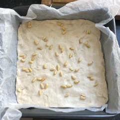 Pine nuts scattered on first layer